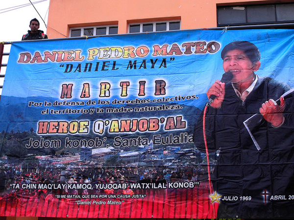 """A banner memorializing Daniel Pedro Mateo is displayed at a protest in the central park of Santa Cruz Barillas on March 14, 2014. Mateo, an indigenous leader who opposed local dam projects, was abducted and killed nearly a year earlier, and his body was found with signs of torture. The banner refers to him as a martyr and hero for the defense of collective rights, the territory, and Mother Nature, and quotes him saying """"If they kill me, let it be for a just cause."""" Photo credit: Luis Miranda Brugo / Alba Sud Fotografia."""