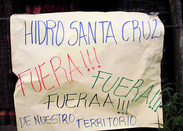 """A sign at a protest against hydroelectric dams in Santa Cruz Barillas on March 15, 2014. The sign refers to the company responsible for a contentious dam that has been linked to murders and detentions of local activists, saying """"Hidro Santa Cruz Out!!! Out!!! Out!!! of our territory"""" Photo credit: Luis Miranda Brugos / Alba Sud Fotografia."""