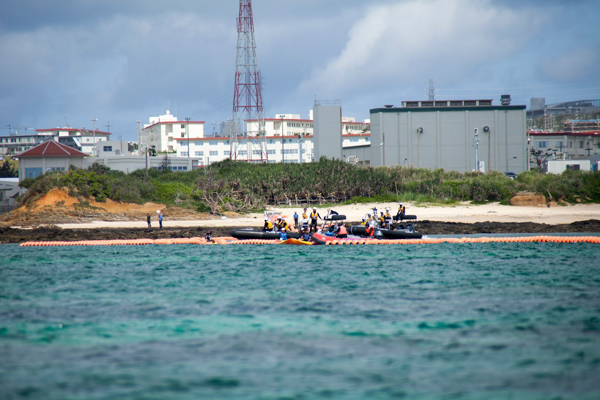 Japanese coast guard vessels approach kayakers near the US base Camp Schwab, where the new US airstrip is planned, on May 17, 2015. The kayakers are protesting construction of the airstrip. Photo credit: ©Greenpeace / Kayo Sawaguchi.