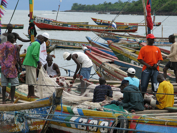 Local fishermen tend their boats in Tombo, a busy fishing village in Sierra Leone. The nation is one of several in West Africa dogged by foreign vessels engaged in illegal, underreported, or unregulated fishing. Photo credit: BBC World Service.