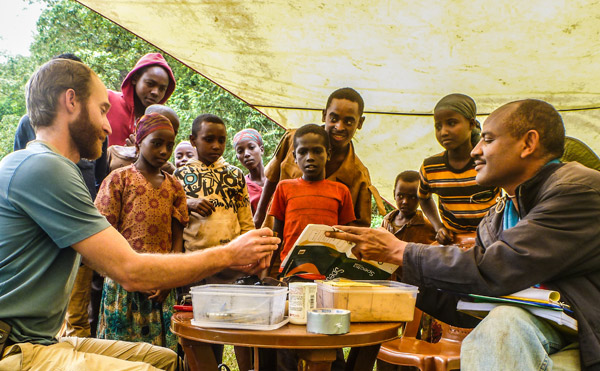 Evan Buechley (left) gives a bird banding demonstration to Ethiopian school children, with the help of Girma Ayalew (right) of the Ethiopia Wildlife Conservation Authority. Outreach and capacity building through hands-on training and job creation are key aspects of our research in Ethiopia. Photo credit: Evan Buechley.