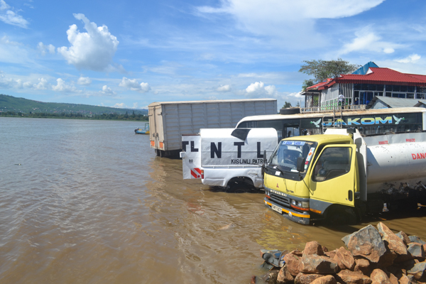 Trucks and a bus are washed right in Lake Victoria at Lwang'ni beach in Kisumu, Kenya. The business is illegal but it goes on with the knowledge of environmental authorities. Photo credit: Isaiah Esipisu.