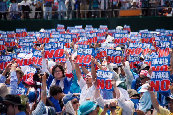Protesters in the Okinawan city of Naha carry signs opposing construction of a new US air base on May 17, 2015. The base would threaten habitat critical for dugongs and is fiercely opposed by local residents. Photo credit: Greenpeace Japan.