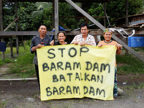 Members of the Penan indigenous group carry a sign stating their opposition to the proposed Baram Dam in Sarawak, Malaysia, in February 2014. Many indigenous communities oppose the dam, which will displace between 6,000 and 20,000 people, according to various estimates. Photo credit: International Rivers.