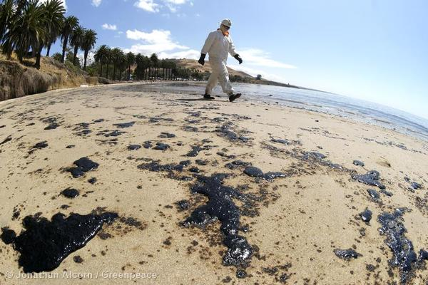 A clean-up worker walks across oil-coated Refugio State Beach on Wednesday, May 20, 2015. Photo credit: Jonathan Alcorn/Greenpeace.